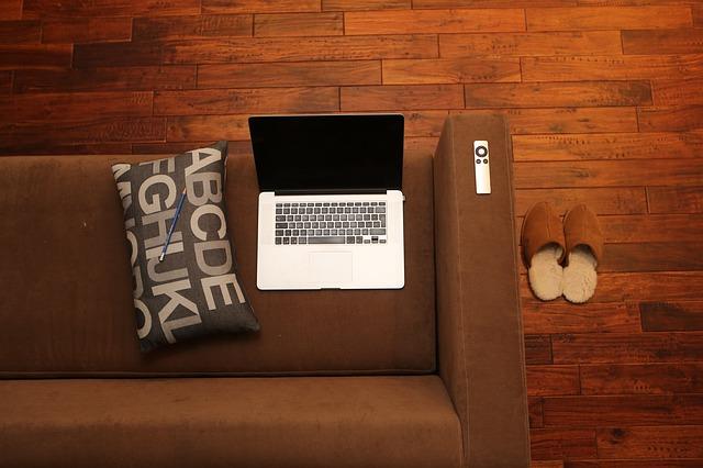 hnědá sedačka, polštářek, notebook, boty